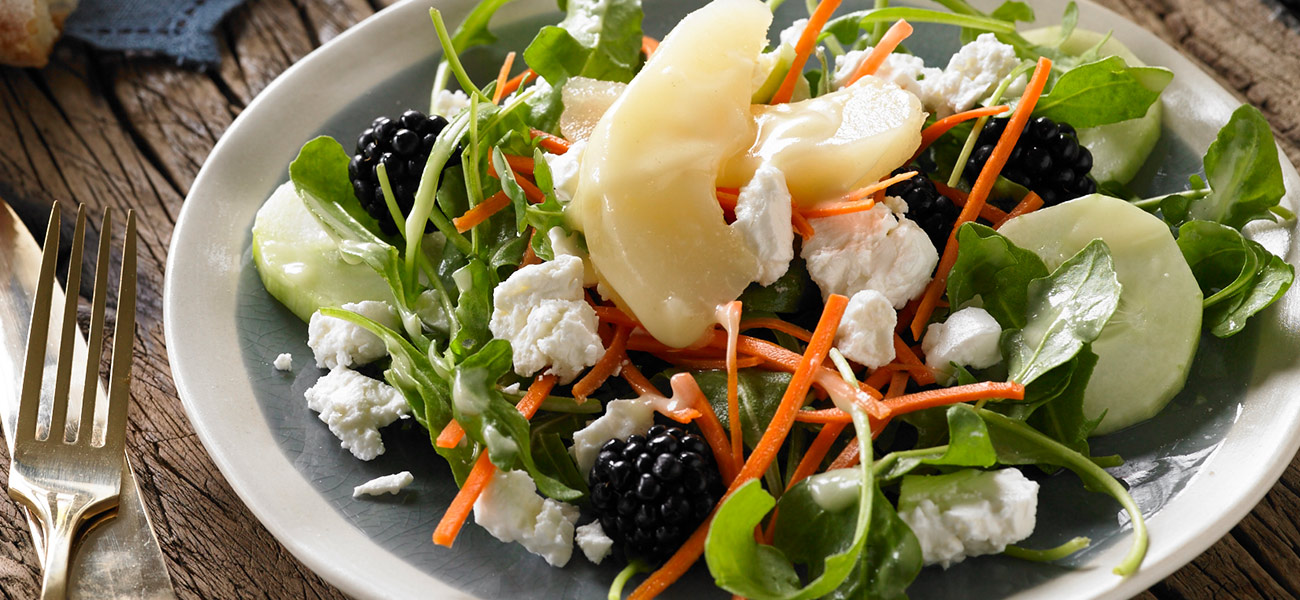 Salad in white bowl topped with pears, carrot sticks on bed of greens.