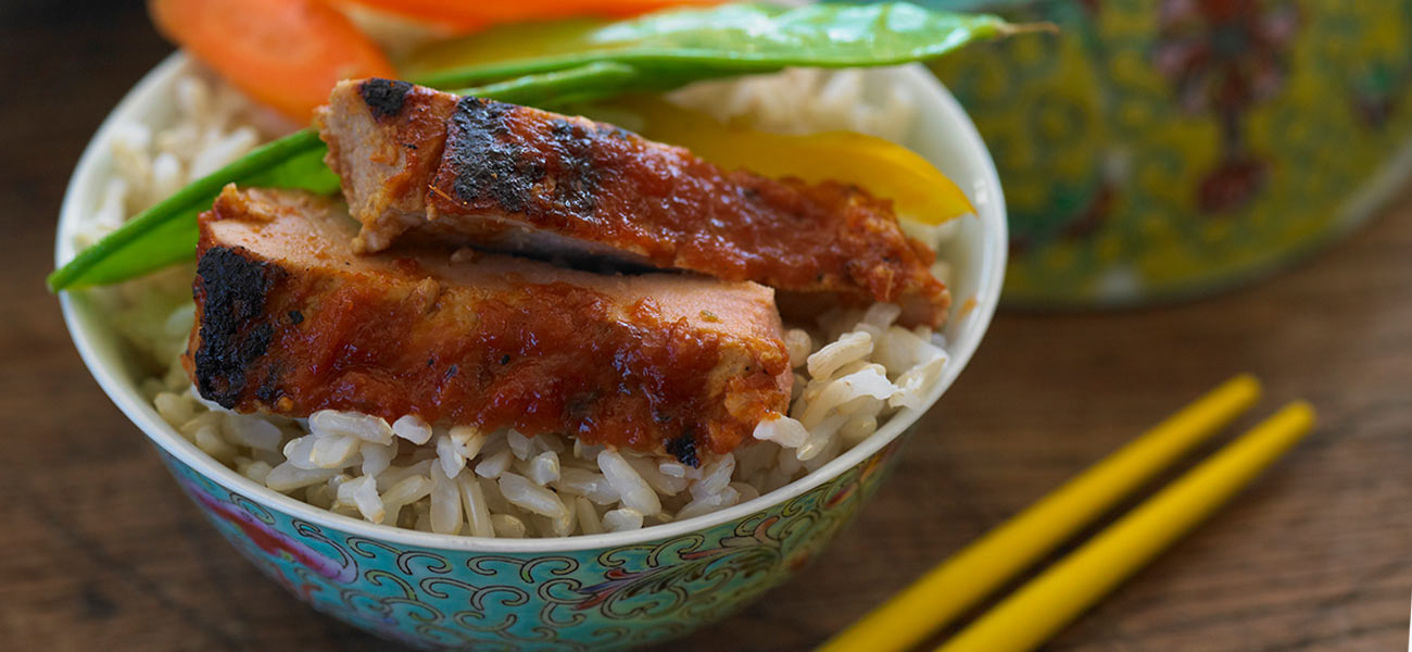 Decorative bowl filled with rice, topped with Asian pear BBQ pork tenderloin.