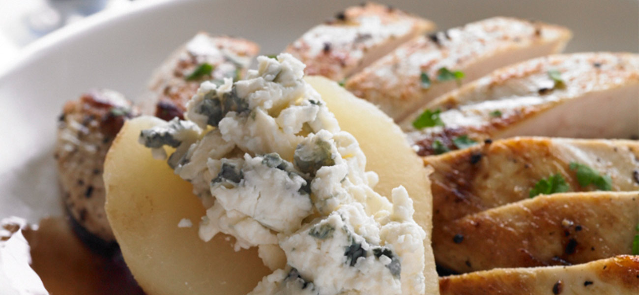 Plated grilled chicken slices with pear topped with blue cheese.