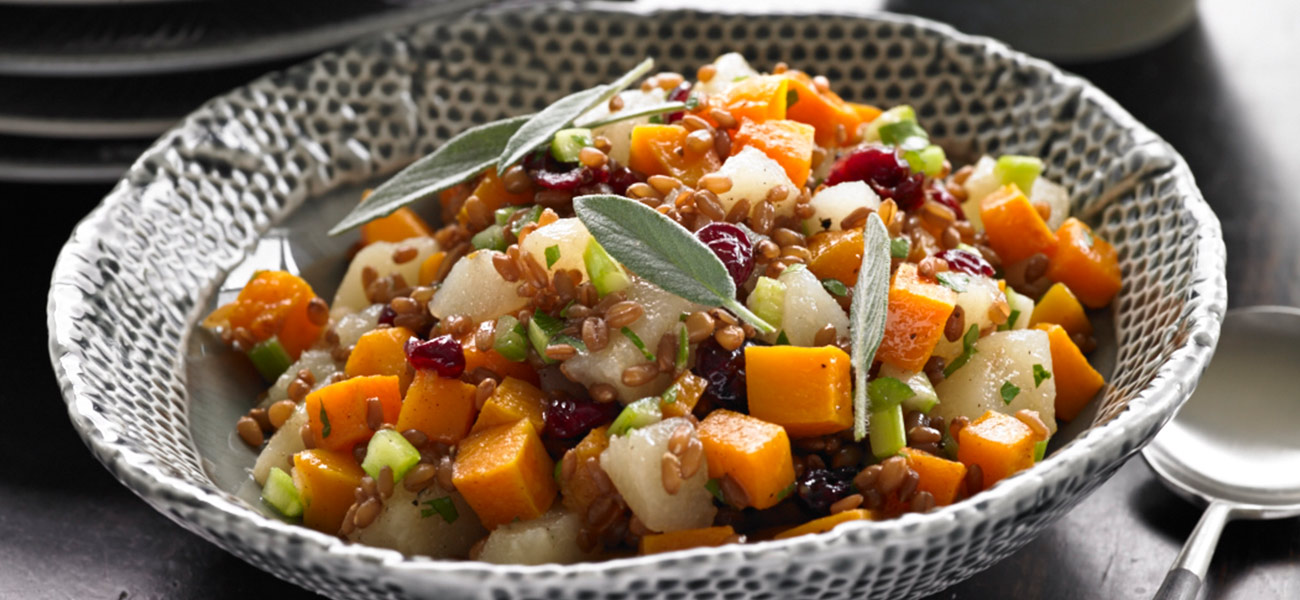 Salad of chopped canned pears, squash and wheat berries in a decorative bowl.