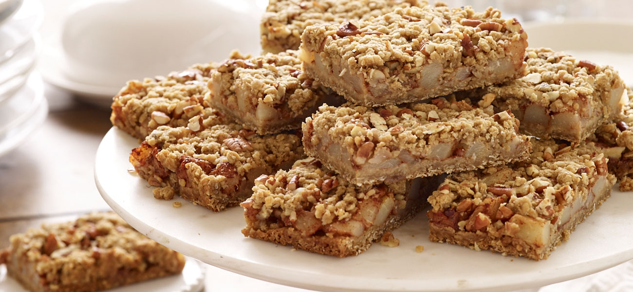 Stack of oat, cinnamon and pear bars on plate.