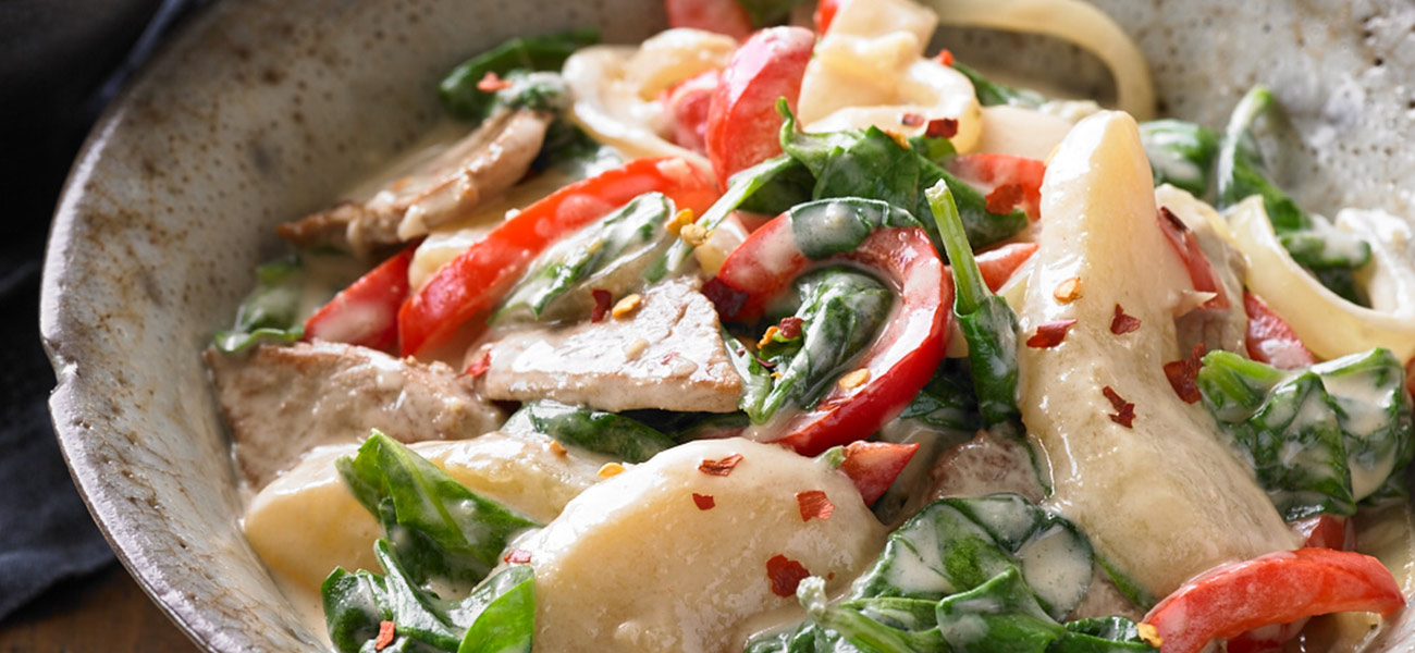 Bowl with stir-fried sliced pears and chicken in coconut sauce with vegetables.