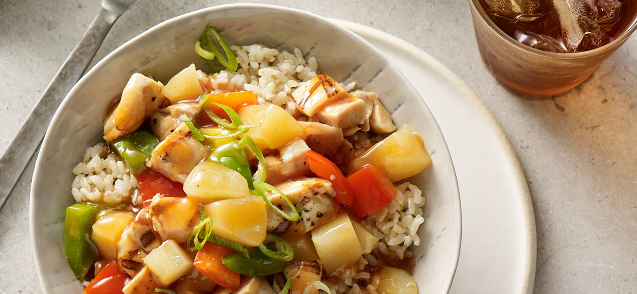 Ceramic bowl filled with brown rice, bright vegetables, chicken and pears.