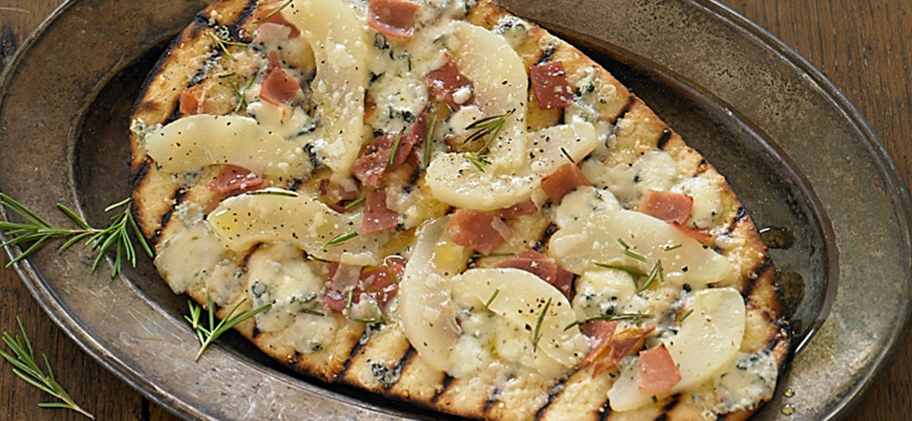Grilled flatbread topped with prosciutto and pear slices.