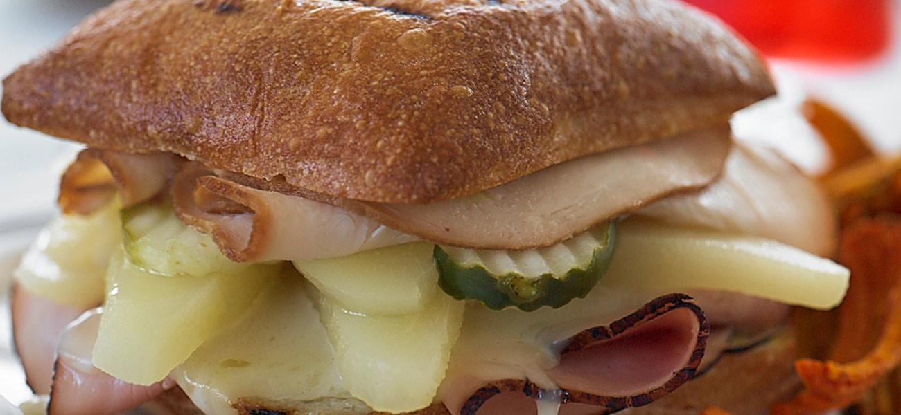 Cubano sandwich with pears on ciabatta bread.