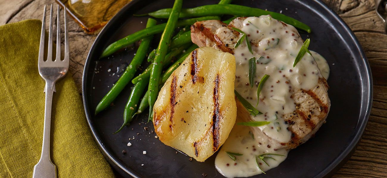 Plated grilled pork chops with pears and mustard cream sauce.