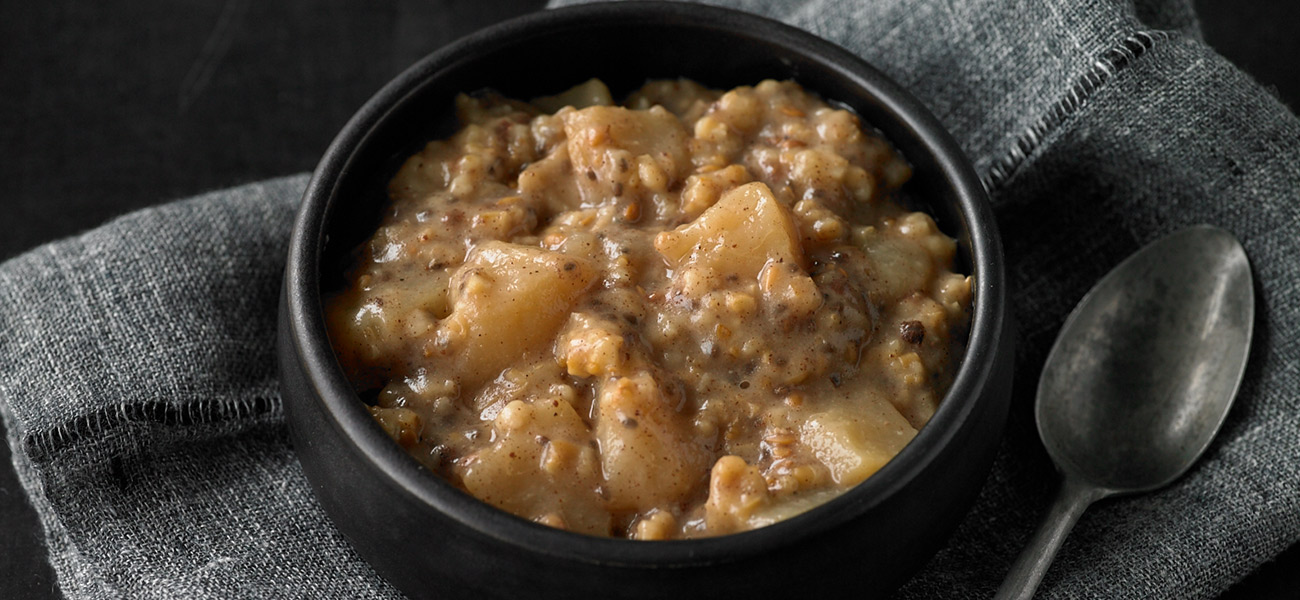 Ceramic bowl of cooked steel cut oats with chopped pears.