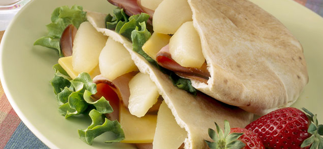Pita sandwich pocket with sliced pears, ham and cheese on a plate.