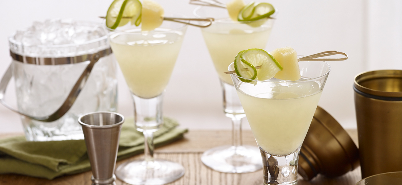 Three martini glasses filled with pear ginger martini, garnished with lime slice and pear chunk.