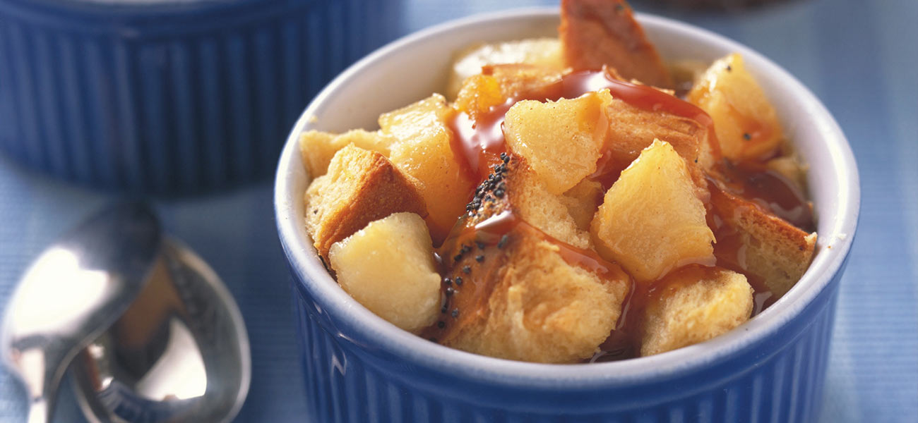 Blue ramekin filled with chunky pear and bread pudding.