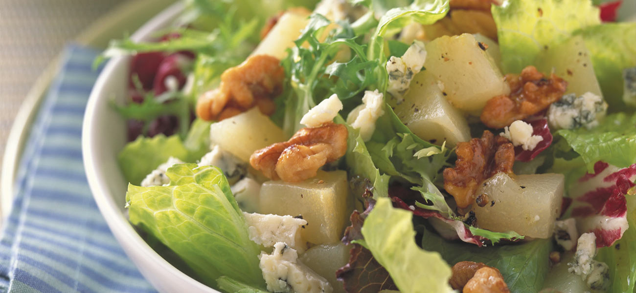 Tossed salad greens with walnuts and pears in a white bowl.