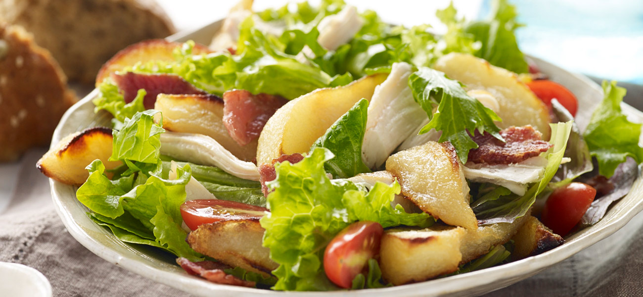 Tossed salad in white bowl with pears and chicken.