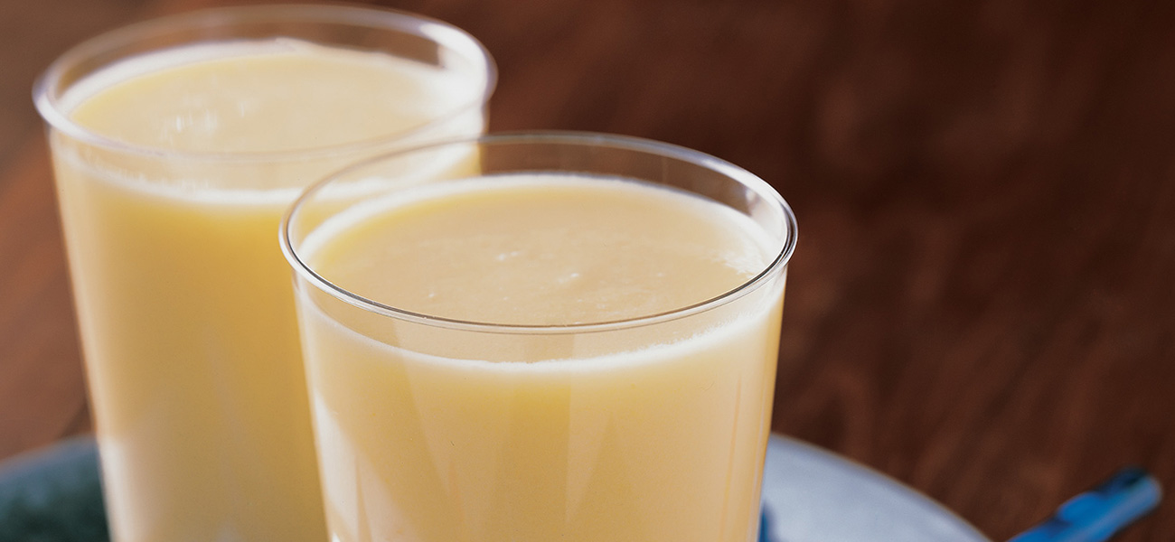 Close up of two glasses filled with smoothie beverage.
