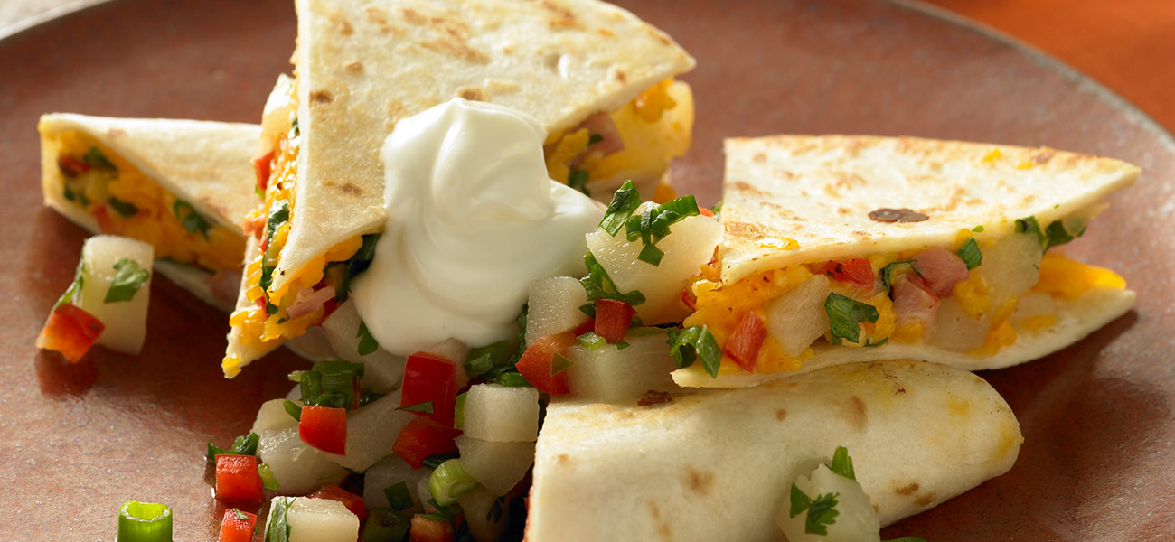 Quesadilla slices with brightly colored vegetables, sour cream and chopped pears.