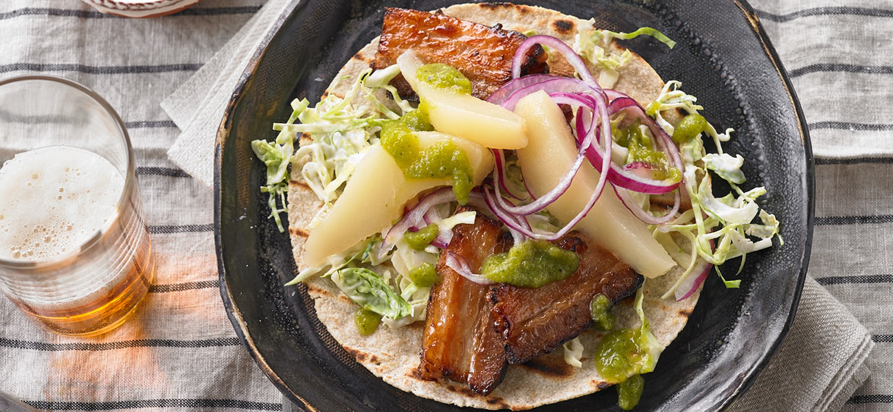 Pair of tacos stuffed with pork belly, sliced pears and veggie salsa on plate.