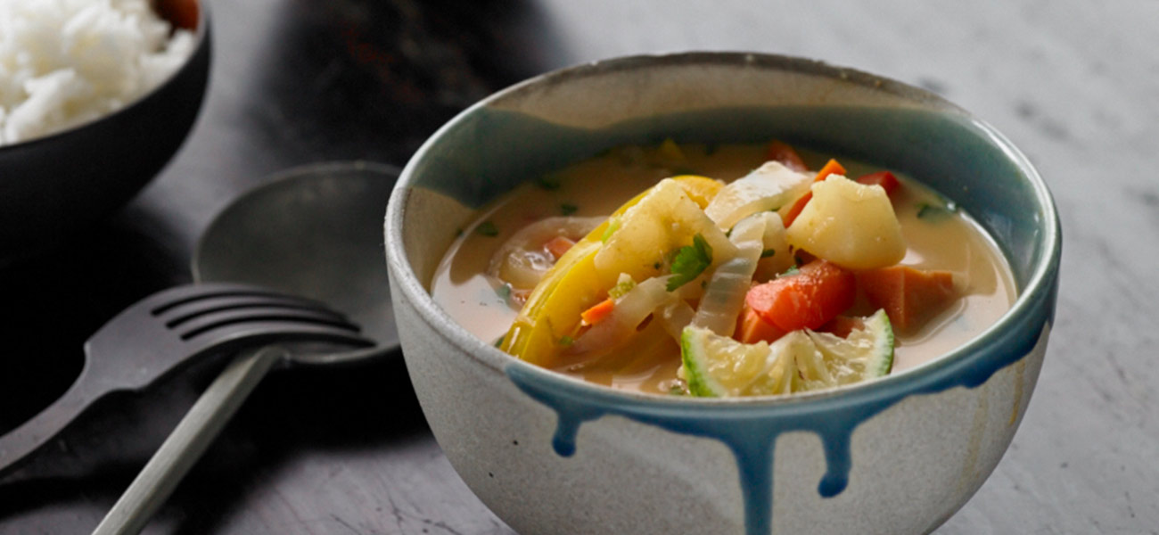 Ceramic bowl filled with colorful vegetables and pears in curry sauce.