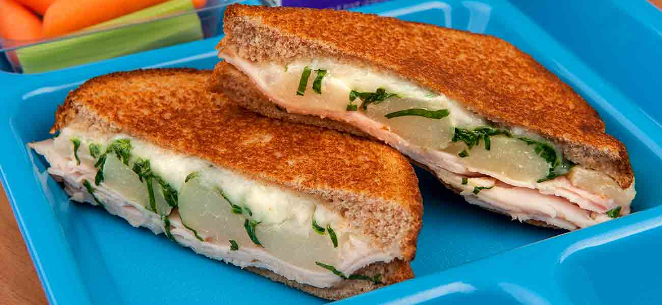 Warm panini sandwich cut on the diagonal with melted cheese and pears on school lunch tray.