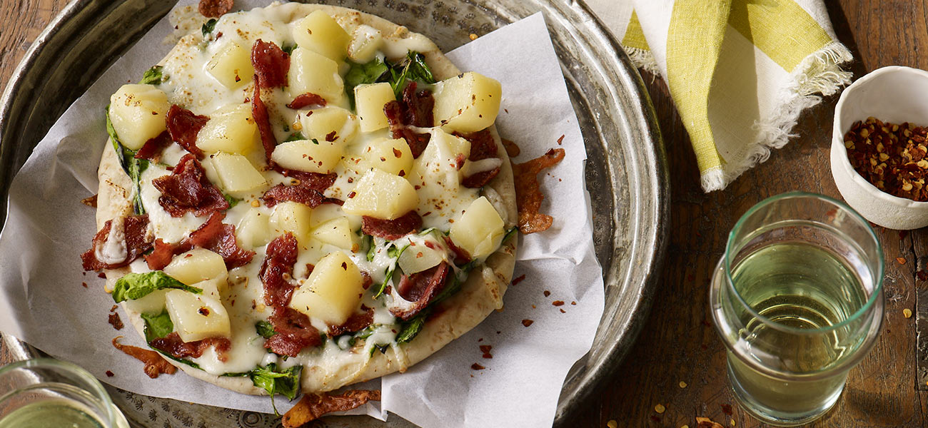 Flatbread topped with pear and bacon on plate.