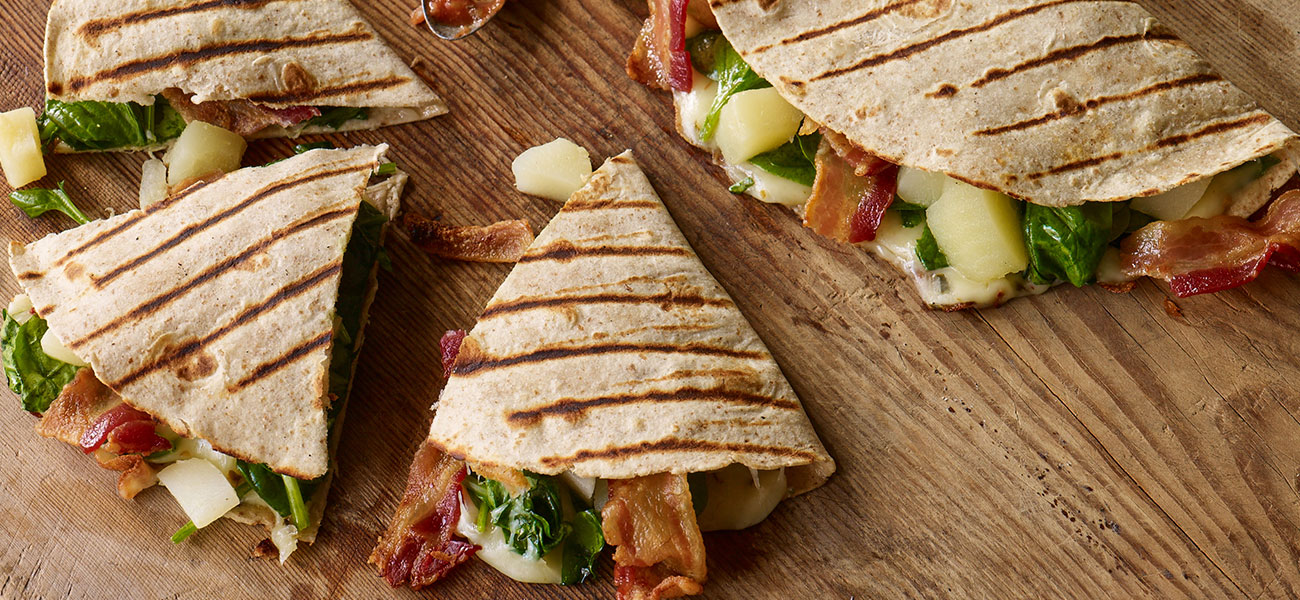 Triangular cut slices of grilled quesadillas filled with pear, bacon, spinach and pepper jack cheese on a wooden board.