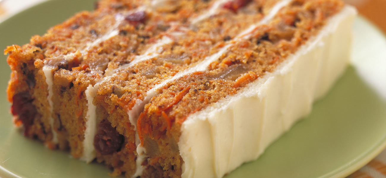 Rectangular slice of four-layer carrot cake with chopped pears in cake layers.
