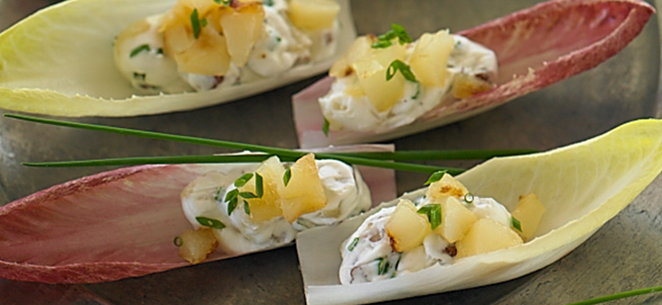 Four pieces of endive lettuce filled with pears and cheeses.