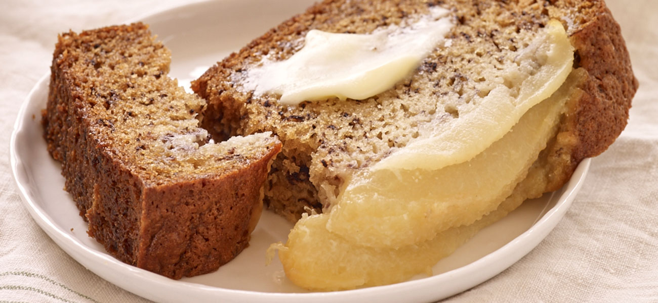 Slice of banana bread made with pears, softened butter on top.