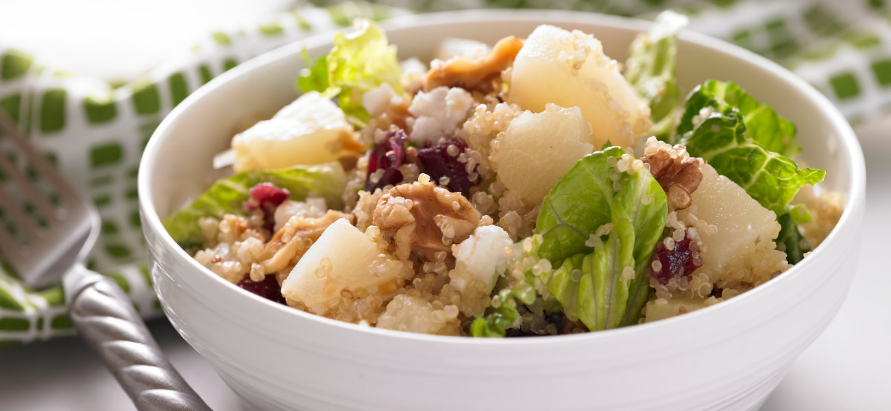 Salad of pears tossed with quinoa and greens in white bowl.