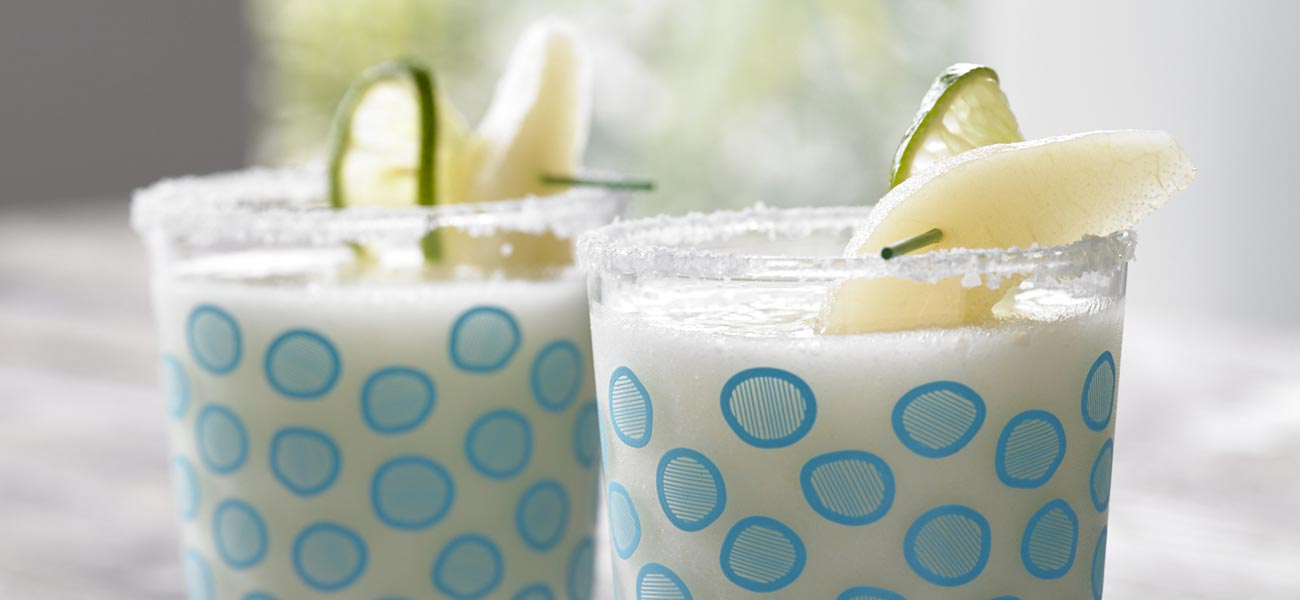 Pear-rita Mocktails in clear glasses decorated with blue dots and a pear wedge garnish