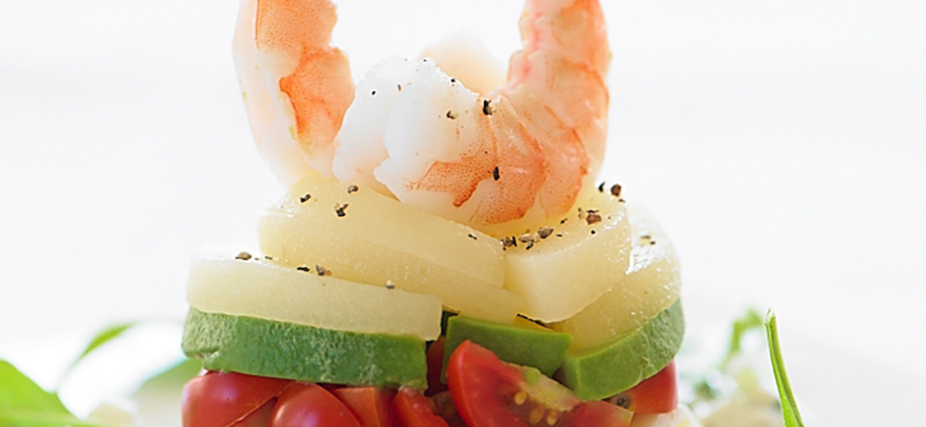Stacked salad with sliced pears and shrimp.