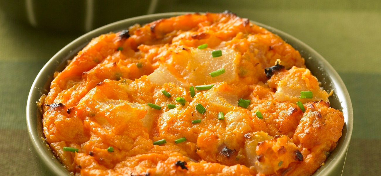 Dish of mashed sweet potatoes and pears topped with chopped chives.