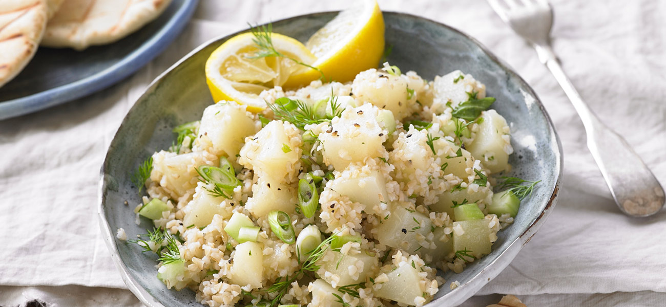 Tabbouleh and chopped pears tossed together with lemon garnish in a salad bowl.