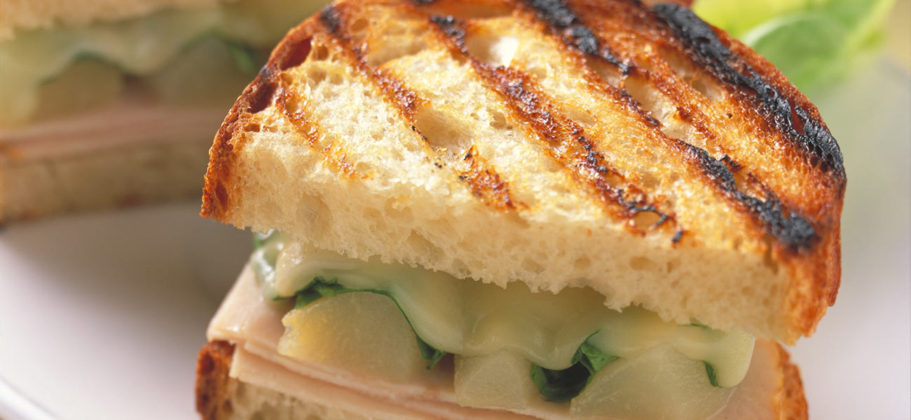 Half panini sandwich with grill marks and melted cheese atop pears on plate.