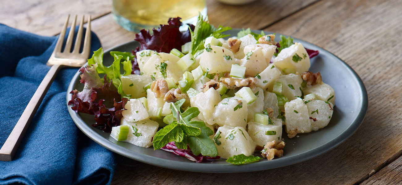 Salad of chopped pears, walnuts and greens on a plate.