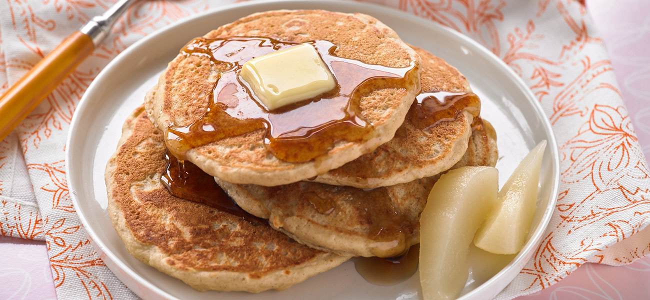 Stack of four golden brown pancakes with syrup and butter on top, pears to the side.
