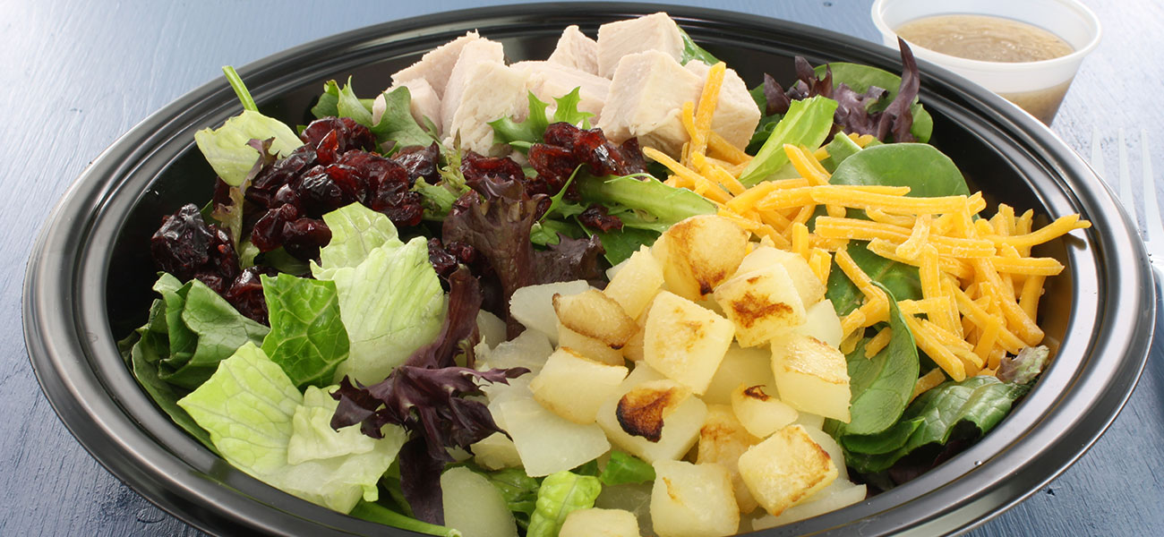 Bowl of salad greens with roasted, diced pears, chicken and cheddar cheese.