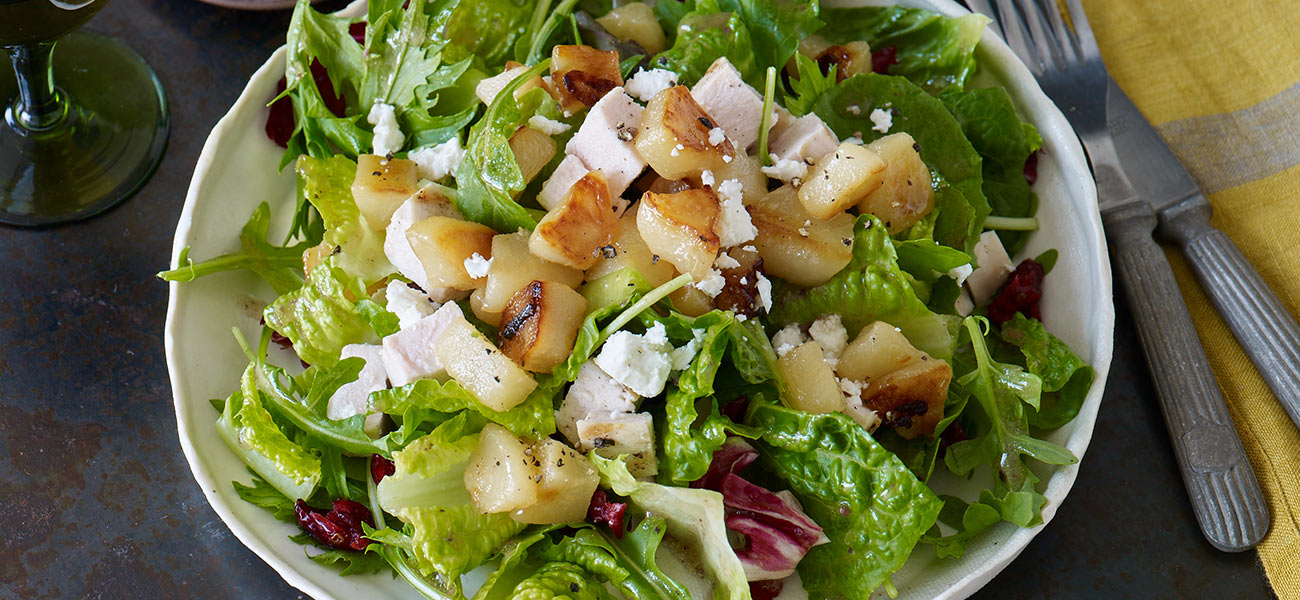 Large salad bowl filled with greens, chopped chicken, pears and feta cheese.