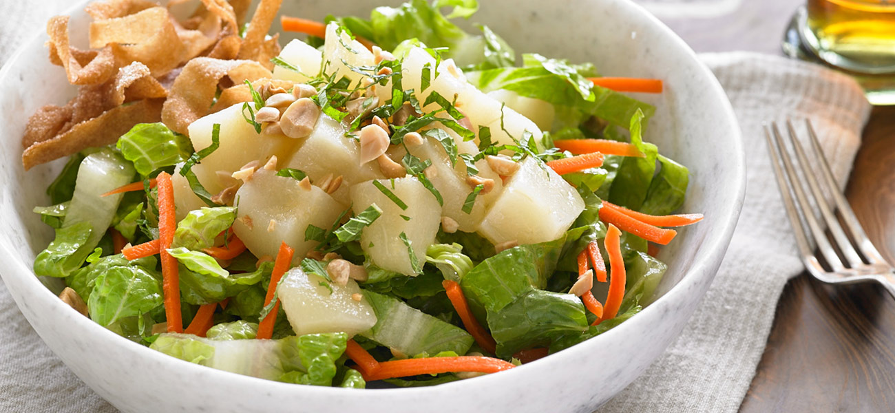 Mixed greens salad with chopped pears, peanuts and carrot matchsticks in bowl.